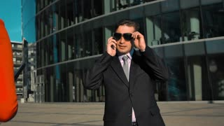Slow motion. Young sexy businesswoman flirt with businessman. Tablet pc and smartphone. Glass business centre building at the bg. Teal and orange dji ronin shot