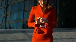 Slow motion: Young sexy businesswoman in red suit and spectacles answering call with smartphone. Teal and orange style. Business centre building background. Stabilize shooting