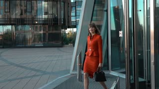 Slow motion. Young sexy businesswoman in red suit with ladies bag and glasses exit from modern business centre building rolling door. Look at the camera. Middle shot. Teal and orange