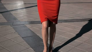 Slow motion. Young sexy pretty brown hair business woman with glasses walking in red suit holding digital pad smiling. Teal and orange sun. Steadicam vertical panorama