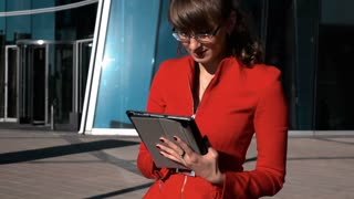 Slow motion. Young sexy pretty brown hair businesswoman in red suit holding tablet pc smiling and look at the camera. Glass business centre bg. teal and orange sun. Steadicam shooting