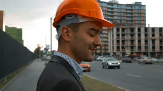 Slow motion. Young successful builder businessman in a orange helmet is making call on the smart phone. Unconstructed building at the background. Close-up steadicam shooting