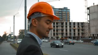 Slow motion. Young successful builder businessman in a orange helmet is making call on the smartphone and smiling. Unconstructed building at the background. Close up steadicam shooting
