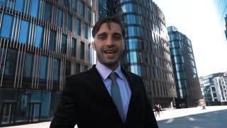 Slow motion. Young successful Businessman in deal suit with tie, shaking Your hand outdoor. He smile and happy of conversation. Teal and orange modern glass business center background. Sunrise