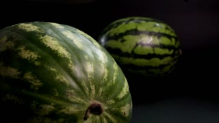 Super slow motion. Two fresh striped green huge big tasty watermelons at black surface and bakground. near Watermelon with sharp knife up near berry fruit. close-up shot