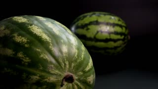 Super slow motion. Two fresh striped green huge big tasty watermelons at black surface and bakground. near Watermelon with sharp knife up near berry fruit. closeup shooting