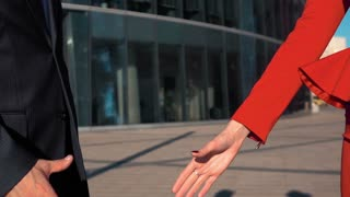 Two Business partners men in black suit and women in red bright dress and manicure doing a handshake with business centre building at the background. Slow-motion close-up