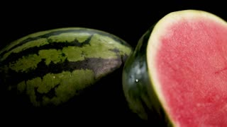Two gigant big green striped wet fresh tasty half sliced water melon with red juicy ripe on black surface and background with water drops Skating around camera. Soft light and shadows
