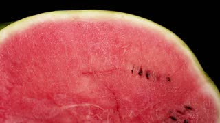 Two gigant huge big green striped wet fresh tasty sliced water-melons with red juicy ripe on black surface and bg. dji ronin camera stabilizer. Soft light and shadows