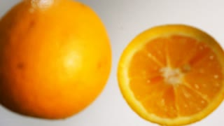 Two parts of juicy tasty oranges falling down into the fresh white milk with stunning explosive splash in slow motion. High-speed camera shooting