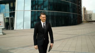 Two successful friendly european businessmen with tablet PC and mobile phone walks towards each other meets and shakes hands with smile. Stunning glossy business centre building at the background