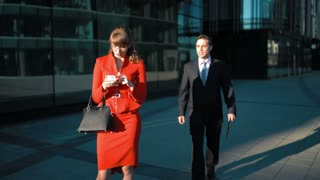 Two young attractive business people. sunset. Sexy brown hair Businesswoman in red dress watch in smartphone. Businessman in suit and tie make deal offer but she reject his offer. Glass Business