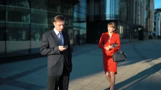Two young attractive businesspeople. Businessman in suit and tie watch in smart phone. Businesswoman try to make offer with digital pad but he reject her offer. Glossy Business centre district bg. 4k