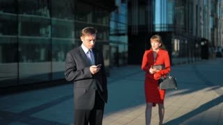 Two young attractive businesspeople. Male in suit and tie watch in smartphone. Slim brown hair red dress Female in spectacles try to make offerbut had reject. Glass Business centre building background