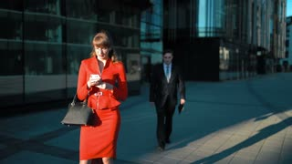Two young attractive businesspeople. sunset. Female in red dress watch in smart phone. Male try to make offer with digital Pad but she reject his offer. Business centre district background. 4k ultra