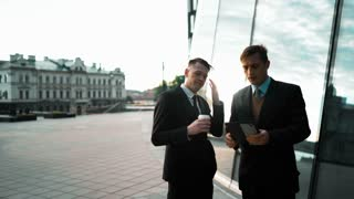 Two young europian businessmen have a deal and communicate. First with tablet PC making offer Second with coffee rejecting his presentation. Glossy business-centre building at the background. Teal and