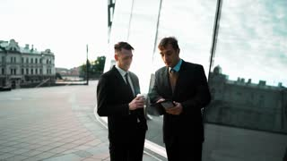 Two young europian businessmen have a deal and communicate. First with tablet PC making offer to second. Second with coffee reject his presentation. Glass business centre building at the background