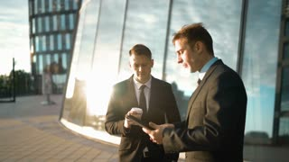 Two Young successful businessmen bidding and discuss their deal and trade. First offer his variation with tablet PC. Second debate with coffee in hand outdoor. Glass business centre building sunset at