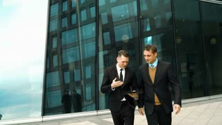 Two young successful businessmen easy communicate and discuss about something fun outdoor. Midday break. Tablet PC in hand. Glass business centre building at the background. Teal and Orange style