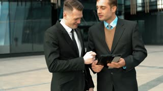 Two young successful businessmen have interecting discussion using and working with tablet PC. Sliding, zooming, scaling screen. Smiling. Glossy business centre building at the background. Teal-and