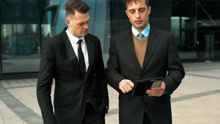 Two young successful businessmen have interecting discussion working with tablet PC. Slide, zoom, scaling screen. Smiling. Glossy business centre building at the background. Teal-and-Orange style