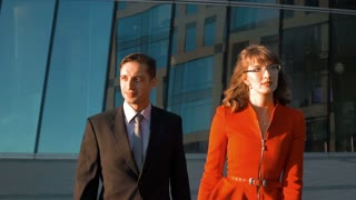 Two Young successful businesspeople, man in balck suit and woman in red dress and spectacles, walk near modern glass building. Teal and orange style. Super slow motion middle shot