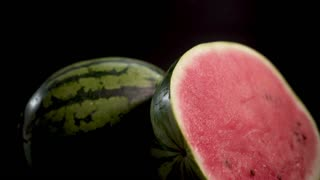 UHD Two gigant huge big green striped wet fresh tasty sliced water-melons with red juicy ripe on black surface and bg 4k. Glidetrack camera. Soft light and shadows