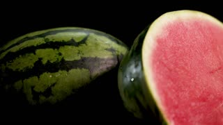 Ultra HD Two gigant big green striped wet fresh tasty half sliced water melon with red juicy ripe on black surface and background 4k. Skating around camera. Soft light and shadows