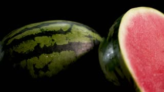 UltraHD Two gigant huge big green striped wet fresh tasty half sliced watermelon with red juicy ripe on black surface and background 4k. Sliding around camera. Soft light and shadows