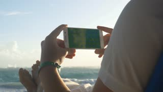 4k uhd Businessman holding horizontal cellphone with empty green screen sitting on the sunbed dressed in suit and shorts on the beach