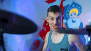 4k uhd Concert rock band performing on stage drummer show his tongue music video punk, heavy metal or rock group. exciting emotions, drive. teal and orange. close-up