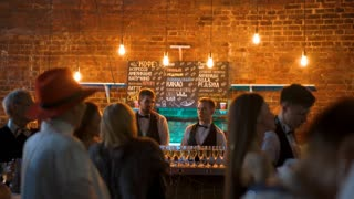4k uhd footage of Two waiters pouring champagne into glasses at the evening event party to guests standing near tables like reception. They have masquerade costumes. Orange lamps bricks loft bg