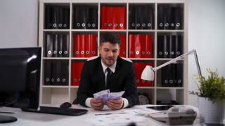 4k UHD. Young attractive businessman wearing a suit sitting in a desk counting euro bills in modern office