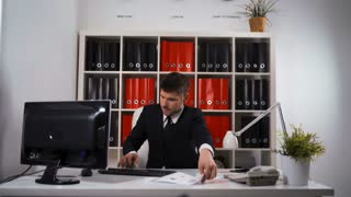 4k uhd. Young successful businessman working hard at office talking mobile and doing many deals typing keyboard of PC. He looks hurry not managed in time . Glidetrack slider cinematic shooting