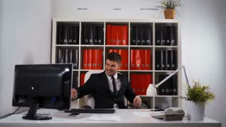4k ultra hd. Cheerful successful attractive sexy businessman sure in himself smiling in his office with raised fists, winning and enthusiasm concept. Euphoria and epic jump with happiness. look at