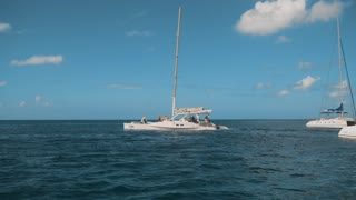 Big luxury cataman sailboat catamaran on the horizon in the beautiful Caribbean sea shooting from other boat on the movie midday sunny. Teal and orange 4k ultra hd style. Blue sky with little clouds
