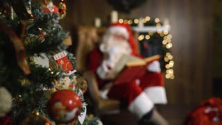 Blurred Santa Claus on xmas eve sitting in armchair hold old red silk album near focused in green christmas tree with toys and lights.