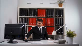 Cheerful successful businessman smiling in his office with raised fists, wins great deal and enthusiasm concept. Cool white room with black and red folders computer ipad tablet documents armchair. 4k