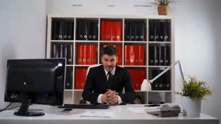 Portrait of happy smiling attractive businessman sitting in office armchair, in black confident suit and tie. Caucasian. Business and success concept. Slider glidetrack moving 4k UltraHD