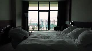 Slow motion. Happy man jumping on bed at hotel in bathrobe. Cool apartments relaxation. Concept relax after hard working. Holiday. 960 fps