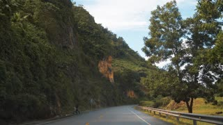 View from the car driving by the asphalt road in Puerto Plata, Dominican Republic. Beautiful landscape of mountains trees blue sky