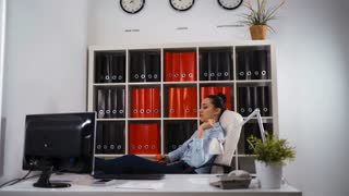 Young business woman yawning at a modern office desk in front of computer, playing with ball, chain reaction, drowsiness, unable to deal with boring job, monday after cool weekends. Slider 4k