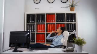 Young business woman yawning at a modern office desk in front of computer, playing with ball, chain reaction, Middle shot legs at the table. Yawning. Glidetrack UHD