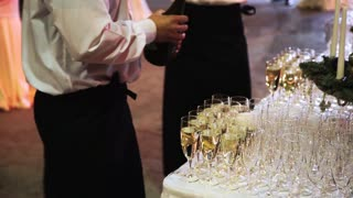 waiters pouring champagne in glass
