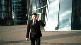 Welldressed young successful businessman with smartphone answering call and start to hurru on meeting. Modern glass business centre district at the background. Teal-and-Orange style. Middle portrait