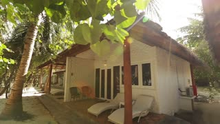 White modern hotel beach bungalow with hay roof and chairs sunbeds. Tropical grass and trees. Afternoon. Sunny Day