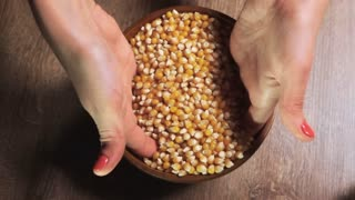 Woman's hand pouring pop corn into a bowl