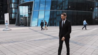 Young attractive businessman shaking white plastic fake hand of his partner. Customer left hand in business man fingers. Sunny afternoon middle static shooting. Glass modern building bg