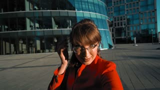 Young attractive sexy businesswoman pov making selfie on smartphone. She in red dress, brown hair with glasses and glass business centre at the background. shooting close-up in 4k Ultra HD