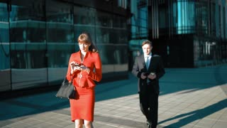 Young businessman in suit and tie make an offer with digital pad to brownhair sexy attractive businesswoman in red dress. She agree smile and shake hand. Glass business centre district background